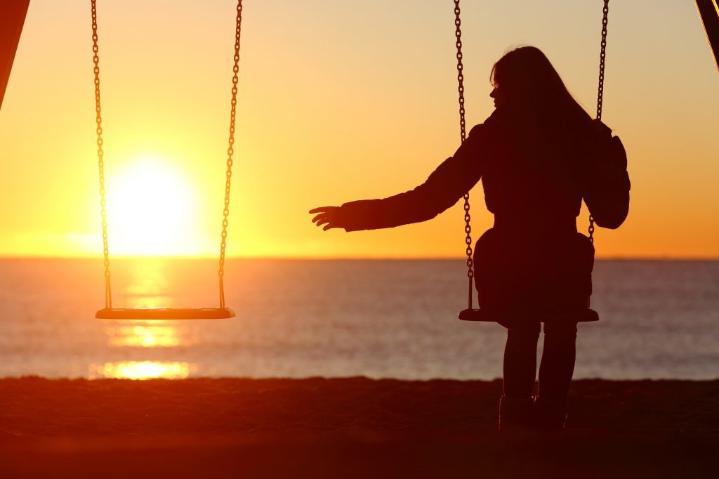 Woman-reaching-for-empty-swing-at-sunset